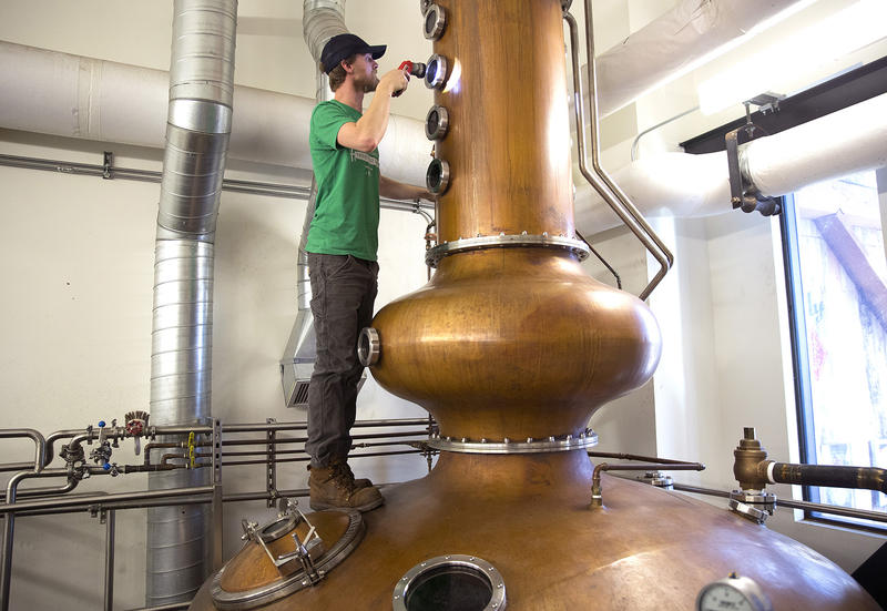 Tyler Pederson, head stillman at Westland Distillery, climbs onto the still to check to see if the spirits were condensing on the still's plates on Monday, March 19, 2018, at Westland Distillery in Seattle.