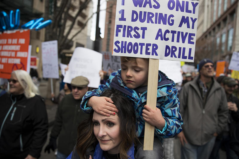 Sarah Samson, of Renton, carries her 4-year-old son Arlo on her shoulders during March For Our Lives Seattle on Saturday, March 24, 2018, in Seattle.
