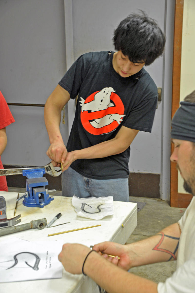 Makah volunteer Alex Wise bending a cibud into shape