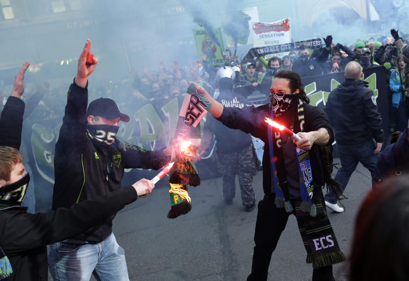 Seattle Sounders fans burn a Portland Timbers scarf during the 'March to the Match' before an MLS soccer match, Saturday, March 16, 2013, in Seattle