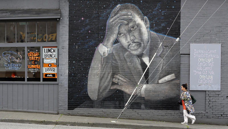 A woman walks past a large mural of the Rev. Martin Luther King Jr. on the side of a diner, painted by artist James Crespinel in the 1990's and later restored, along Martin Luther King Jr. Way, Tuesday, April 3, 2018, in Seattle.