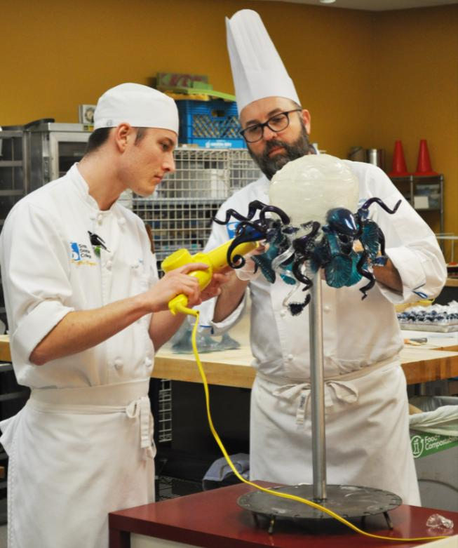 Chef Christopher Harris (right) with student Joey Bale work on a replica of Dale Chihuly's glass chandelier for the artist's birthday cake.