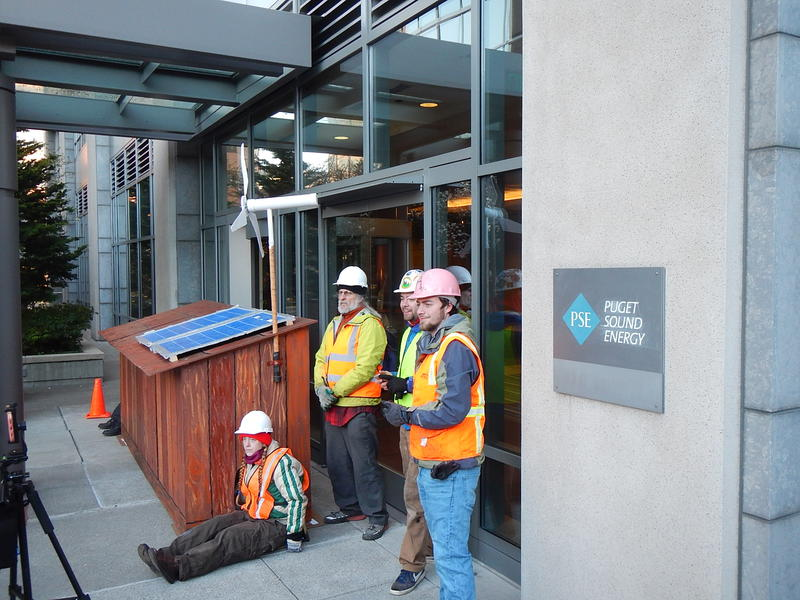 Protesters dressed as construction workers and a mini-longhouse they erected to block Puget Sound Energy's doors