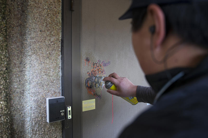 Kapono Alani sprays graffiti remover onto a door to the Old Crematorium on Thursday, March 1, 2018, at Evergreen Washelli Cemetery in Seattle.