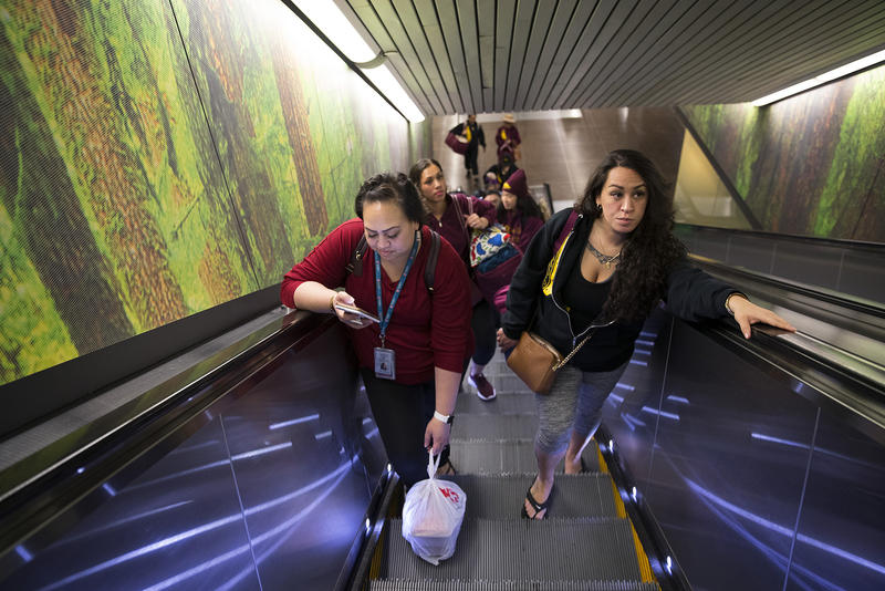 Tanya Jose, left, and Leilani Kaaiwela-Pedreira ride the escalator at Seattle-Tacoma International Airport before flying to Hilo on Friday, March 30, 2018.