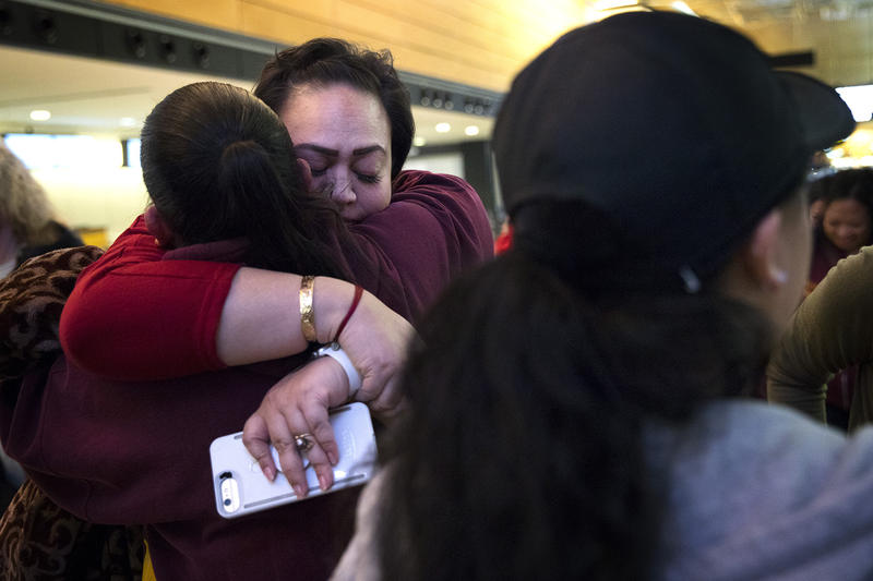 Tanya Jose, center, hugs Lynn Whalen on Friday, March 30, 2018, before the group leaves for the Merrie Monarch Festival in Hilo, at Seattle-Tacoma International Airport.