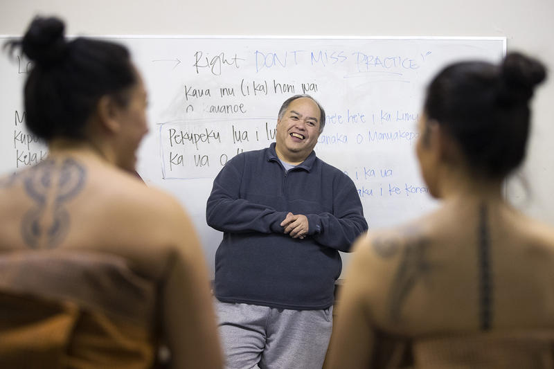 Kumu Hula Kamaile Hamada, center, laughs as he checks to make sure the lengths of all of the dancer's Kahiko dresses match on Thursday, March 22, 2018, at the halau in Federal Way.