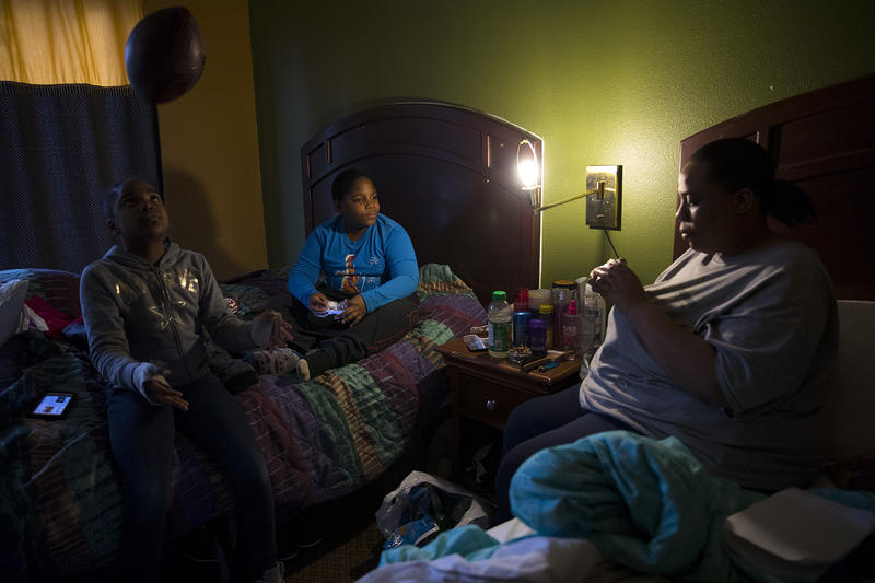 Ja'Shay Macklin, 10, left, plays with a football as her twin brother Ja'Sean watches their mother Stephanie Macklin-Jones work on a rubik's cube in their room at the Everspring Inn on Monday, March 26, 2018, on Aurora Avenue North in Seattle.