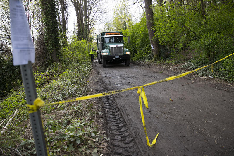 A former encampment in Ravenna is roped off as crews clear out the area with a garbage truck on Wednesday, April 18, 2018, in Seattle.