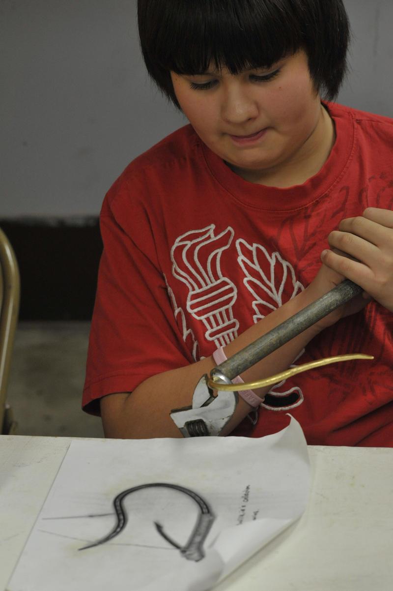 Makah volunteer Ollie Kallappa, Jr., bending a cibud into shape