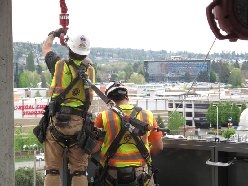 Workers wear harnesses and a line to protect them from falls as they install glass walls at the edge of an office tower under construction in Renton.