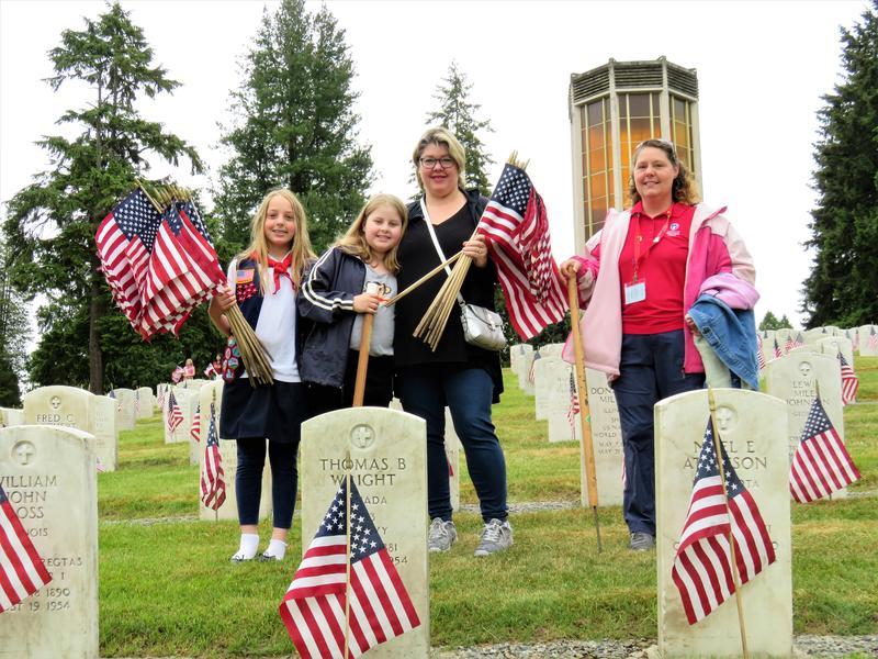 Grace Bartelheimer, Carris Grace, Elizabeth Grace, and Heather Bartelheimer distributed flags.
