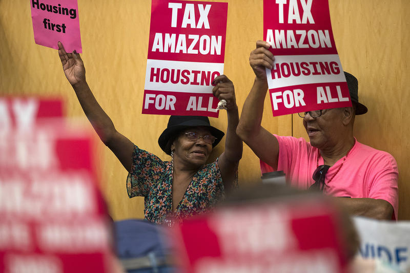 Diana Easter, left, and Milton Easter raise Tax Amazon signs in the air on Monday, May 14, 2018, during a head tax vote at City Hall in Seattle.