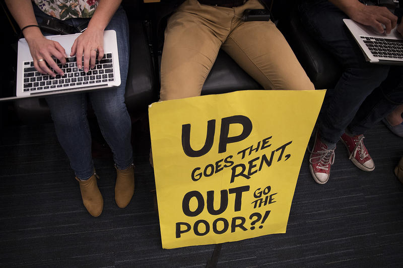 A sign rests at Matthew Lang's feet during the head tax vote on Monday, May 14, 2018, at City Hall in Seattle.