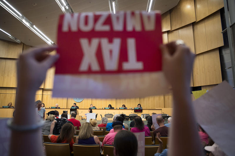 Caitlin Lee raises a Tax Amazon sign in front of Seattle City Council members on Monday, May 14, 2018, during a head tax vote at City Hall in Seattle.