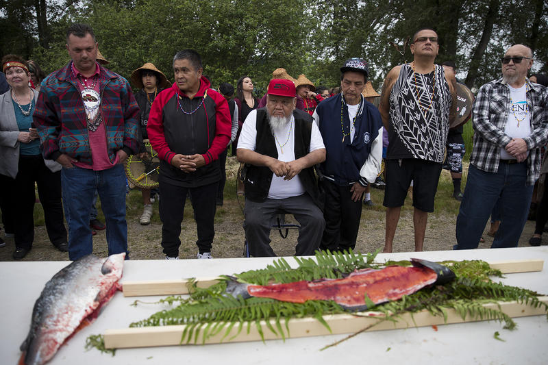 Elders from the Puyallup Tribe including Les Nelson, center, at a first salmon ceremony on Tuesday along the Puyallup River in Tacoma.