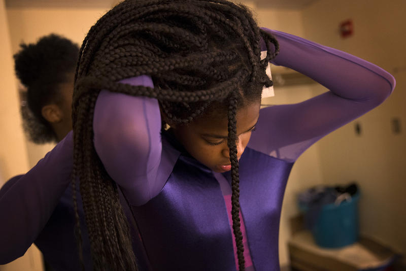 Yizjuani Watson, 11, has help with her costume from Simya Gibson, 13, during a rehearsal on Tuesday, May 15, 2018, at Rainier Beach high school in Seattle.