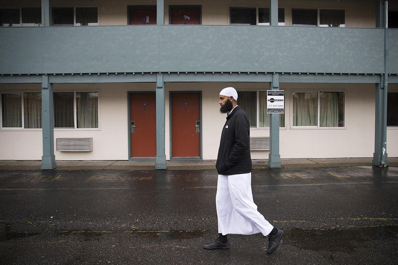 Ahmed Hussein walks in front of the Knights Inn Motel on Monday, April 16, 2018, in Tukwila.