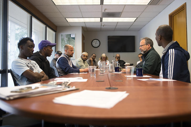 Business owners and members of the community, including Tawfik Maudah, third from left, speak with Tukwila City Administrator David Cline, second from right, on Thursday, April 19, 2018, at Tukwila City Hall in Tukwila.
