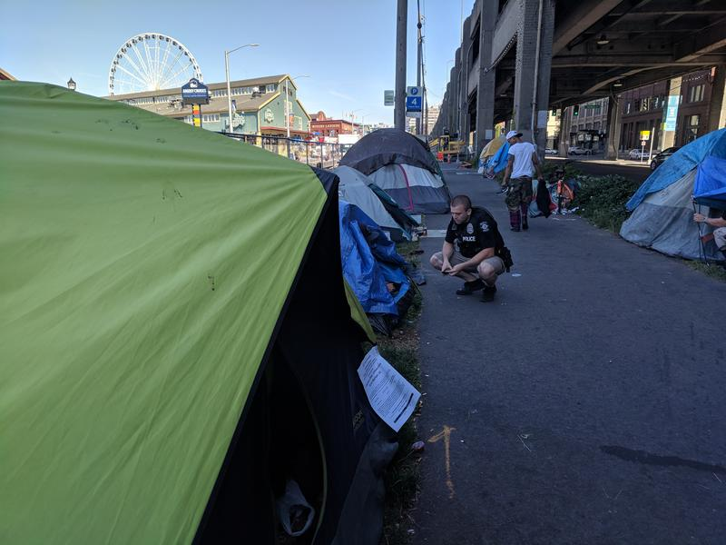 Seattle Police Officer and Navigation Team member Brad Devore offers services and shelter to campers