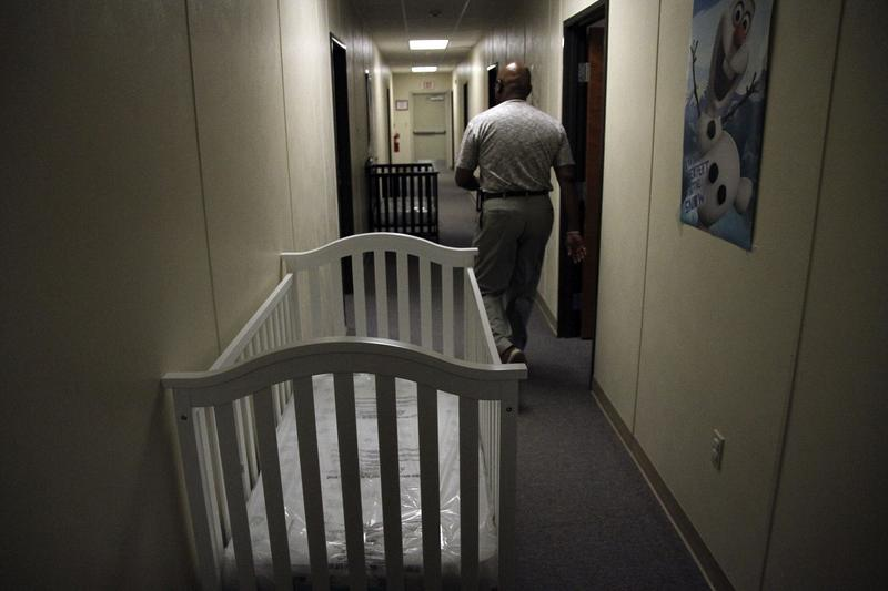 A federal employee walks past cribs inside of the barracks of a family detention center in Artesia, New Mexico, for those crossing the border. This photo is from 2014, when attorney Danielle Rosché volunteered there.