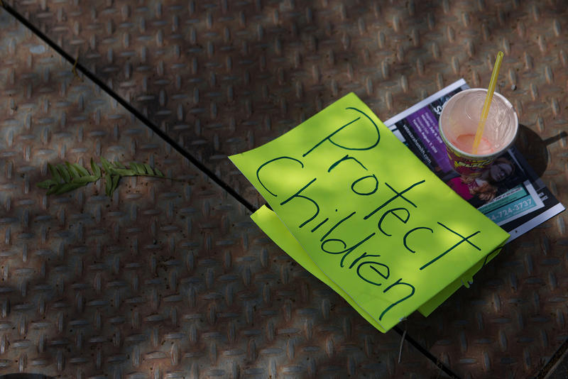 A sign rests on the ground during the Solidarity Day protest outside of the Federal Detention Center in SeaTac.