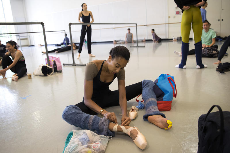 Amanda Morgan puts her point shoes on before company class with instructor Peter Boal on Thursday, May 24, 2018, at the Pacific Northwest Ballet in Seattle.