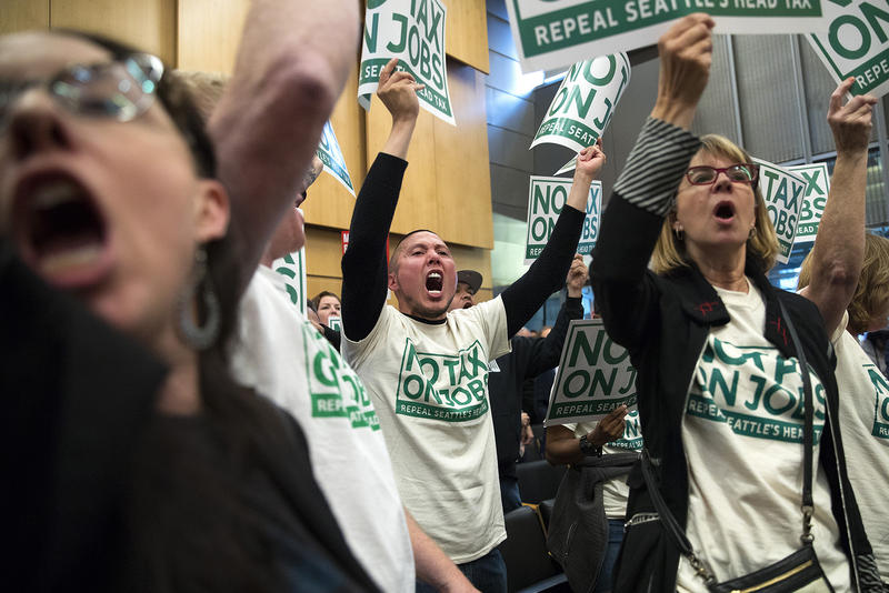 Chris Cruz, center, cheers after the head tax vote on Tuesday, June 12, 2018, inside City Council Chambers at City Hall in Seattle.