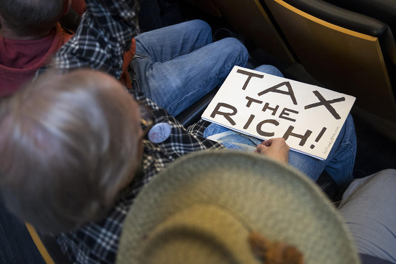 Brent McFarlane holds a Tax The Rich sign on Tuesday, June 12, 2018, inside City Council Chambers at City Hall in Seattle.