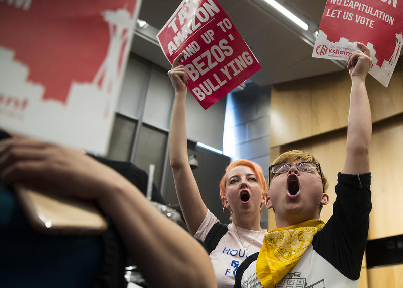 Emerson Johnson, right, leads a chant on Tuesday, June 12, 2018, inside City Council Chambers at City Hall in Seattle.