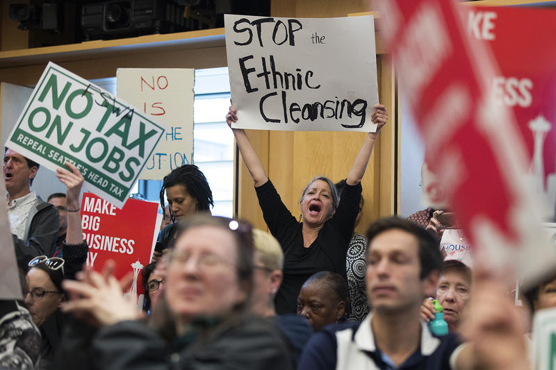 Fern Renville holds a 'Stop the Ethnic Cleansing' sign on Tuesday, June 12, 2018, inside City Council Chambers at City Hall in Seattle.