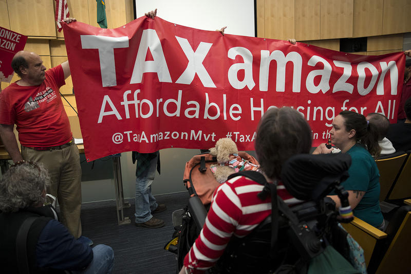 A Tax Amazon sign is held up in front of council members on Tuesday, June 12, 2018, inside City Council Chambers at City Hall in Seattle.