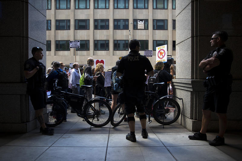 Seattle police officers block the entrance to the Immigration Court building before Maru Mora's hearing on Tuesday, June 26, 2018, on 2nd Avenue in Seattle.