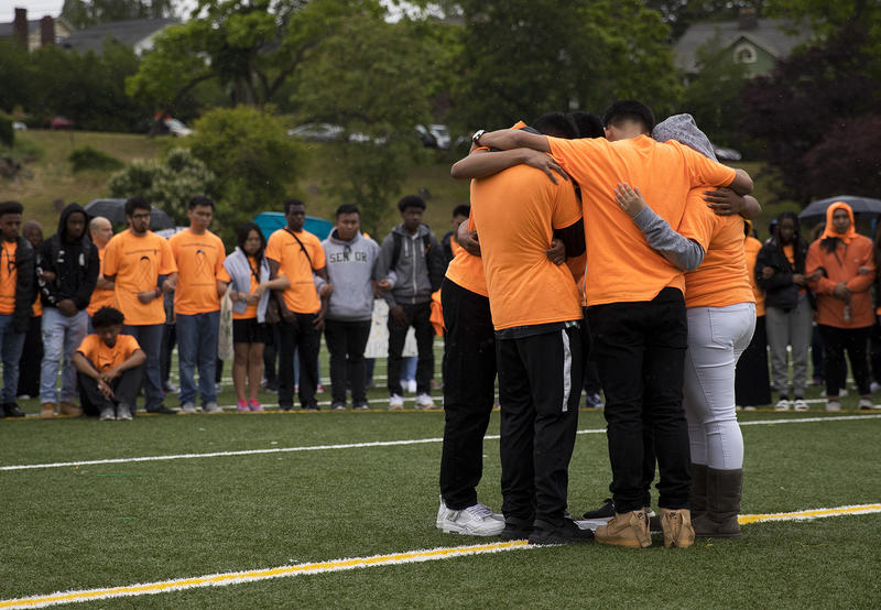 Friends and classmates of Ryan Dela Cruz embrace on Friday, June 8, 2018, after an assembly and demonstration calling for an end to gun violence at Franklin High School in Seattle.