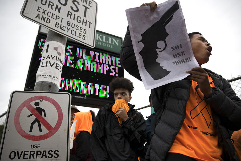 Franklin senior Marc Muñoz, 18, right, holds a sign up for passing cars during a demonstration on Friday, June 8, 2018, outside of Franklin High School in Seattle.