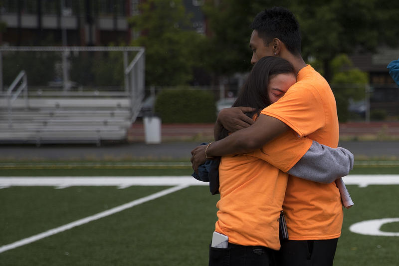 Amy Nguyen, 17, left, and Noel Antonio, 18, right, embrace after gathering to remember their classmate and friend, Ryan Dela Cruz, on Friday, June 8, 2018, at Franklin High School in Seattle.