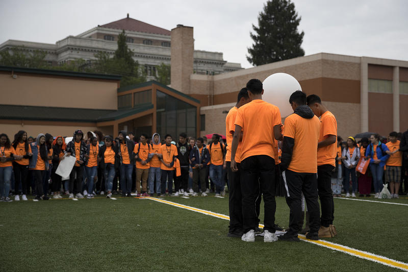 Friends and classmates of Ryan Dela Cruz embrace before releasing a balloon on Friday, June 8, 2018, after an assembly and demonstration calling for an end to gun violence at Franklin High School in Seattle.