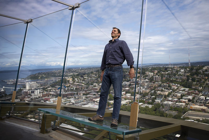 Derek Hanson stands on a glass bench on the observation deck of the Space Needle on Tuesday, June 5, 2018, in Seattle. Hanson asked KUOW what would happen to the Space Needle in the event of an earthquake.