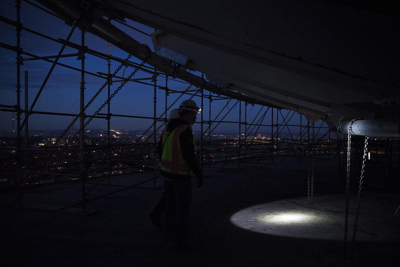 A construction worker uses a flashlight to exit the suspended scaffolding below the new rotating restaurant at the Space Needle on Monday, November 6, 2017, in Seattle.