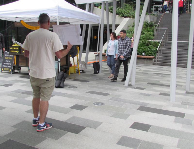 """No Tax on Jobs"" volunteer Mike Hamstra seeks signatures near Amazon banana station. Amazon opposed the employee head tax."
