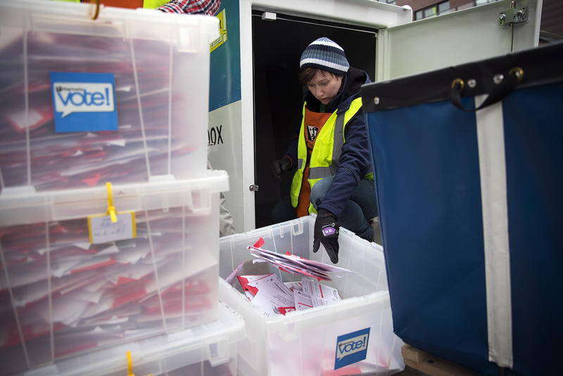King County Elections employee Josephine Ruff unloads a  full ballot drop box outside of the Seattle Public Library on Tuesday, November 7, 2017, in Ballard.