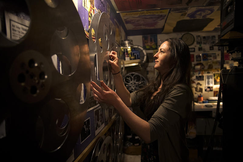 Sarah Kleehamer, a volunteer projectionist, removes a reel from the wall on Tuesday, June 12, 2018, at Grand Illusion Cinema in Seattle. Kleehammer has been volunteering at the cinema for 15 years.