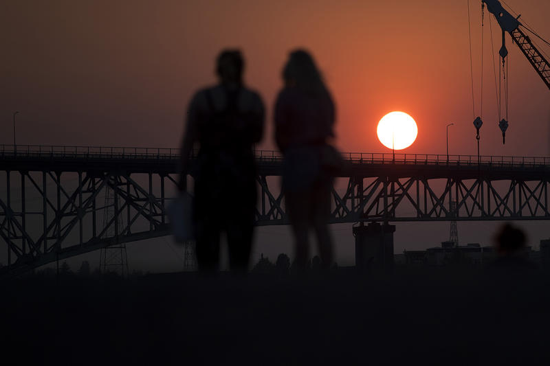 People watch as the sun sets from Gas Works Park on Monday, July 30, 2018, in Seattle.