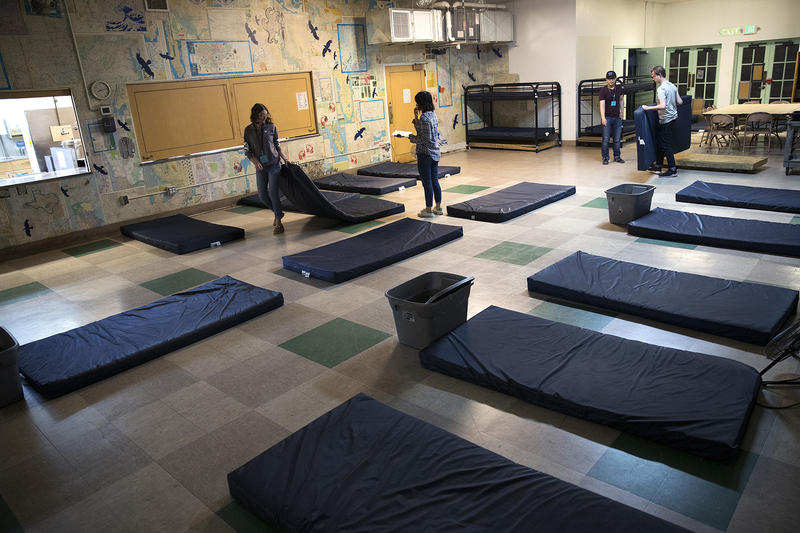 Volunteers set up sleeping mats at ROOTS Young Adult Shelter on Tuesday, July 10, 2018, in Seattle. The shelter can accommodate up to 45 young adults a night.