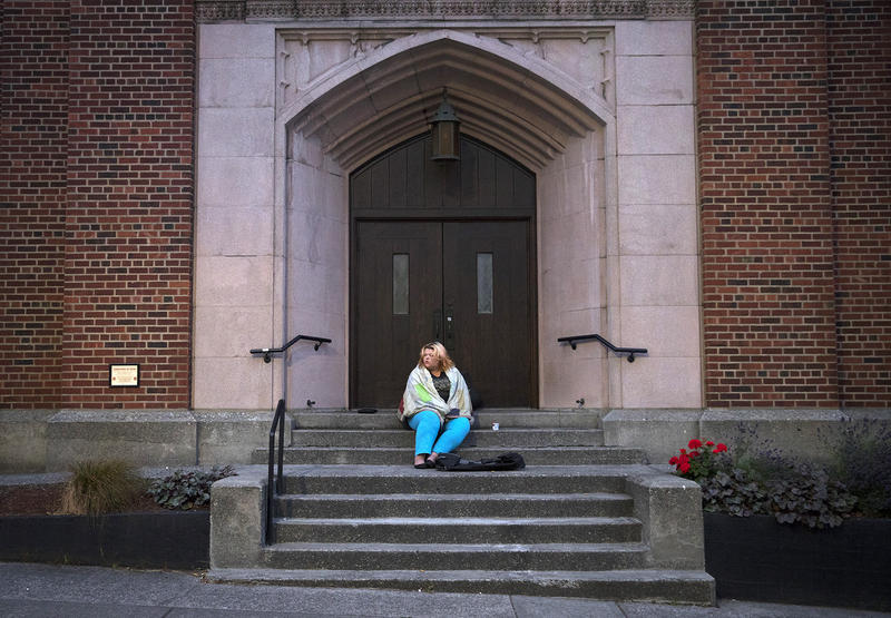 Milee Ballweg, 20, sits on the steps of a University District church where she sleeps just after 5 a.m. on Wednesday, July 11, 2018, in Seattle.