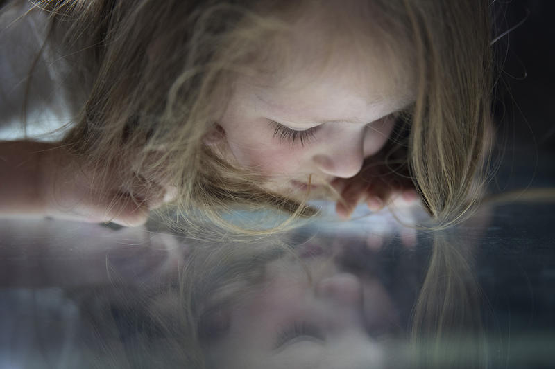 Samantha Sikora, 4, lays on the rotating glass floor of the Space Needle on Friday, August 3, 2018, in Seattle.