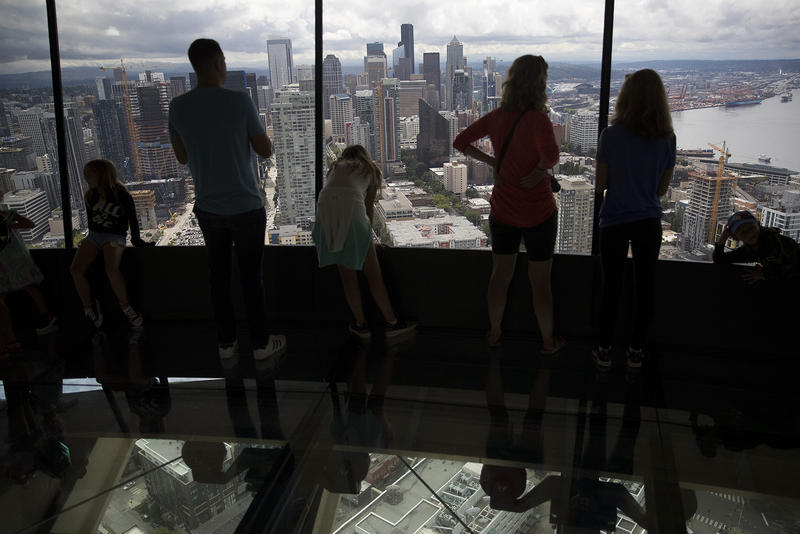 Crowds gather to experience the world's first revolving glass floor at the Space Needle on Friday, August 3, 2018, in Seattle.