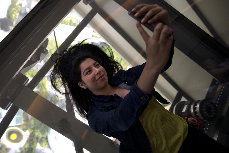 Raquel Piceno, 19, lays on the rotating glass floor to take a selfie at the Space Needle on Friday, August 3, 2018, in Seattle.