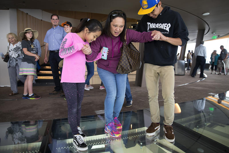 Samantha Ramirez, 9, left, and Benjamin Ramirez, 16, right, help their mother, Sheila Ramirez, center, to step onto the rotating glass floor at the Space Needle on Friday, August 3, 2018, in Seattle.