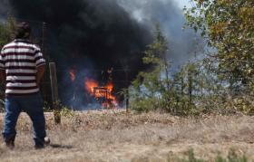 An onlooker watches as flames consume a piece of farm equipment in Cedar Park.